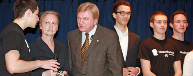 Schulsprecher Philipp Epstein unterhält sich mit Bouffier und Schulleiterin Balser hört aufmerksam zu